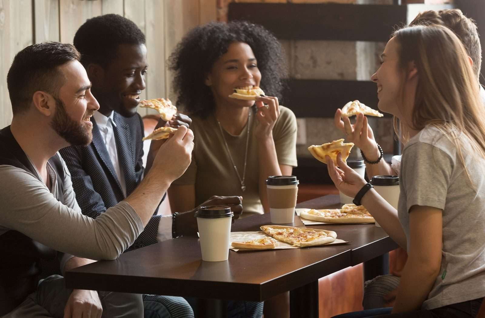 Friends eating pizza and drinking coffee